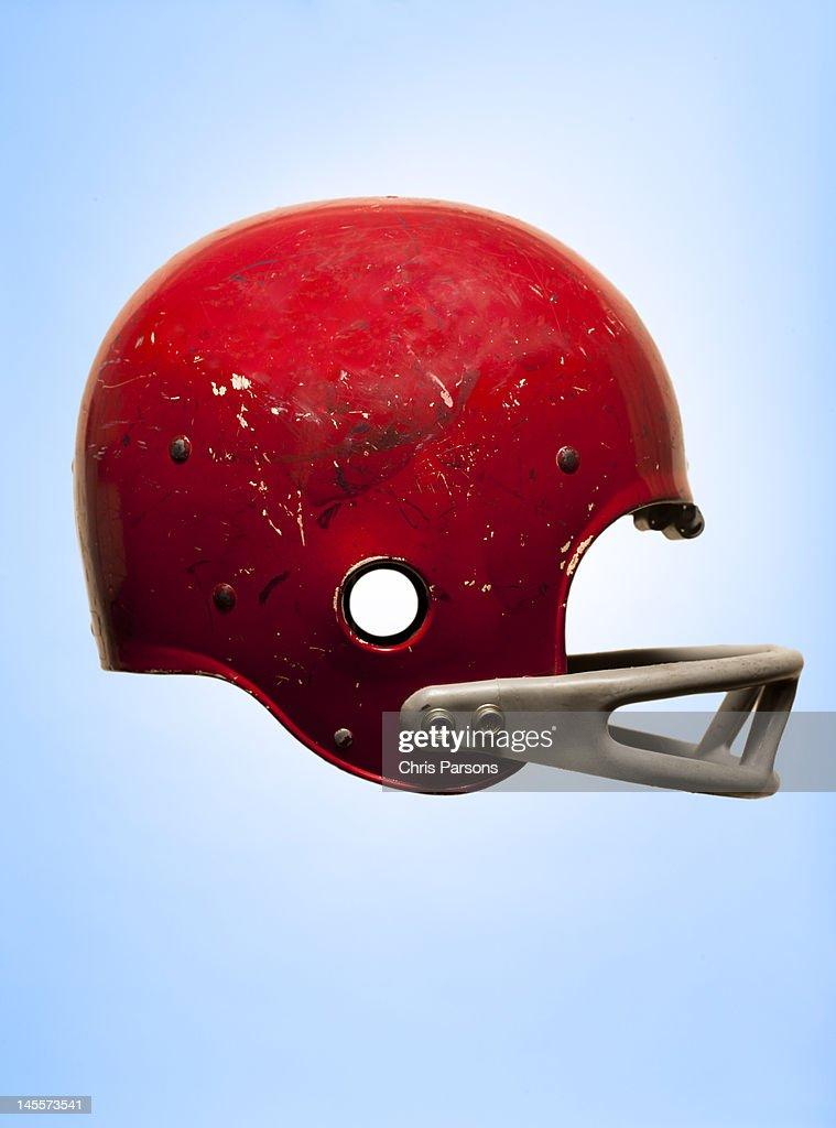 Antique football helmet on blue background : Stock Photo