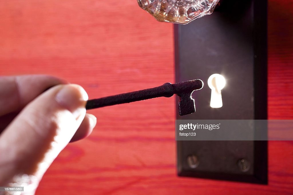 antique glass door knob and skeleton key light in keyhole stock photo