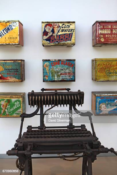 Antique Italian gelato wafer boxes and a castiron conemaking machine on display at the Carpigiani Gelato Museum on March 28 2017 in Bologna Italy...