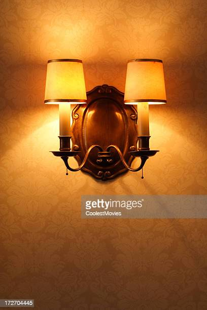 Antique Lighting Fixture Against Old Patterened Wallpaper