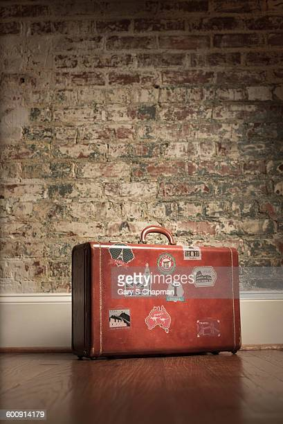 Antique luggage in front of brick wall
