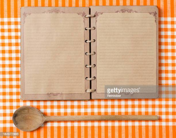 Antique notebook and wooden spoon on orange tablecloth