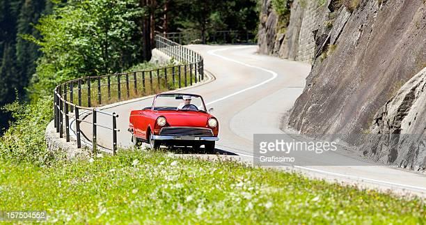Antique red vintage car on alpine road