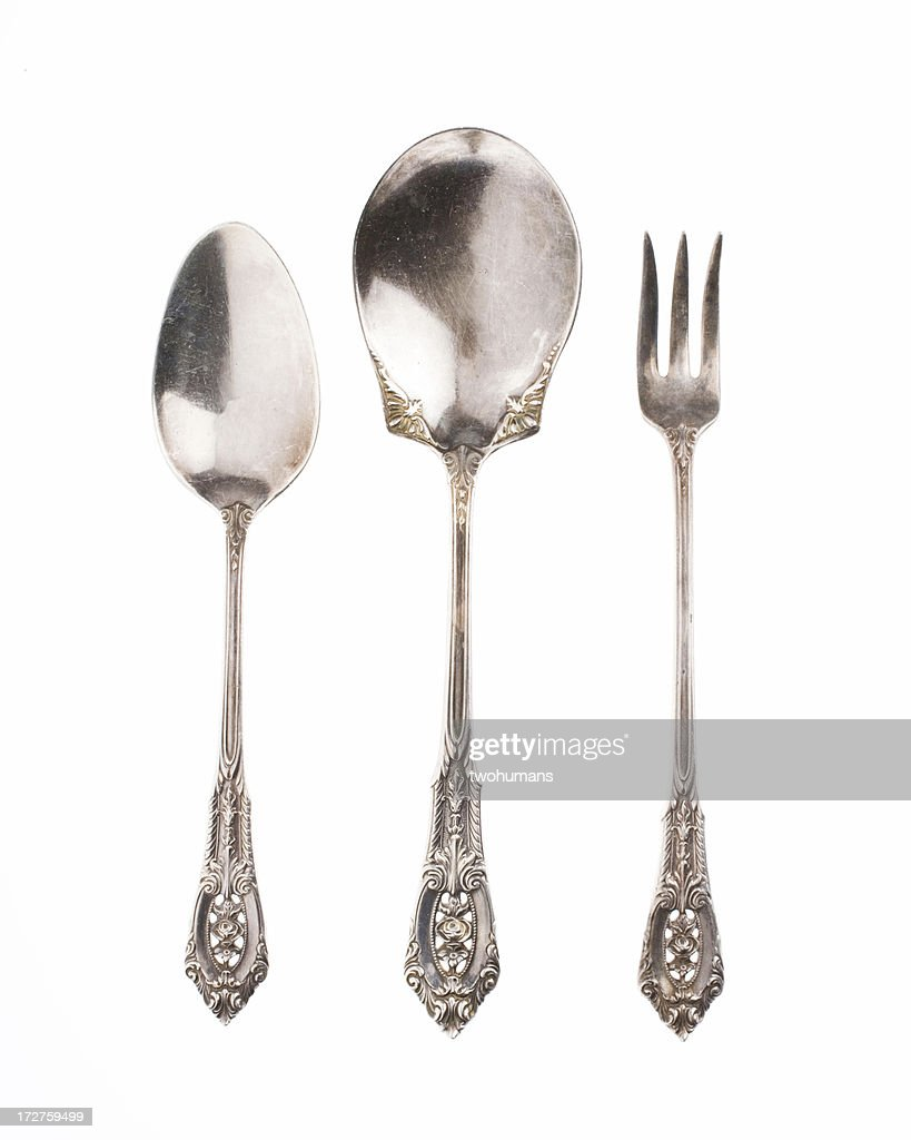 Antique silver spoons and fork on white background