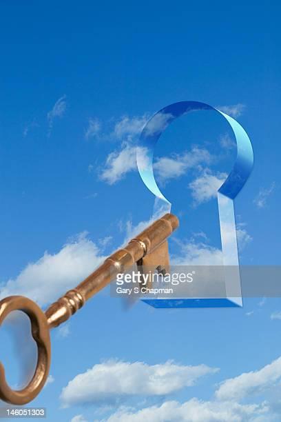 Antique skeleton key going into cloud keyhole