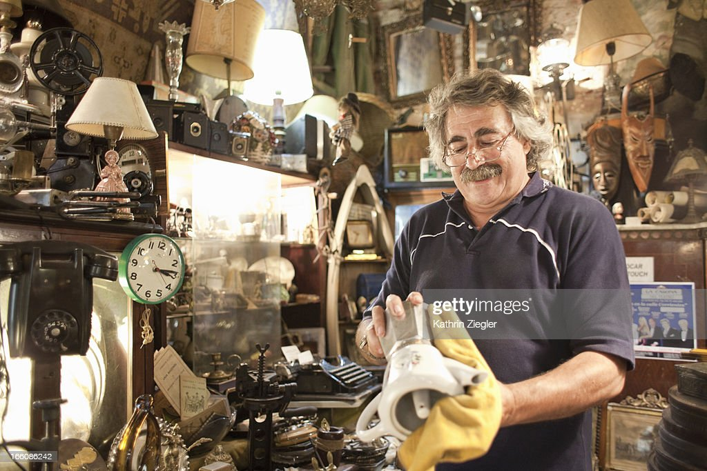 antique store owner polishing old coffee maker