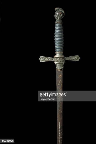 Antique sword on black with ornate handle and rusty blade.