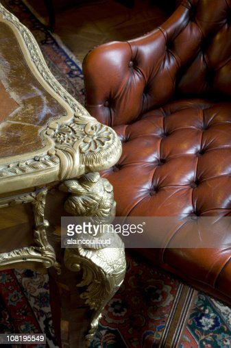 Antique Table And Chesterfield Leather Armchair With ...