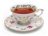 Antique tea cup full of tea on white background