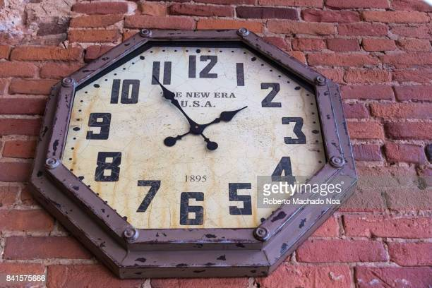 Antique wall clock decorating a red brick wall in a cafeteria in Old Montreal