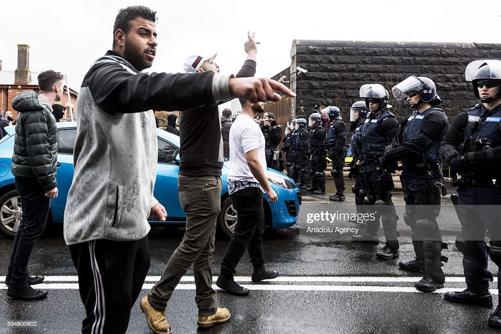 Anti-Racism protestors walk through traffic as they antagonise True Blue Crew members in front of riot police during a 'Say No To Racism' protest and a counter 'Stop the Far Left' rally in Coburg Melbourne, Australia on May 28, 2016. Seven men were arrested after a violent brawl erupted between rival protesters at an anti-racism rally in Melbourne's inner-north. Anti-Facists clashed with Anti-Islam nationalists who go by the name 'True Blue Crew'.