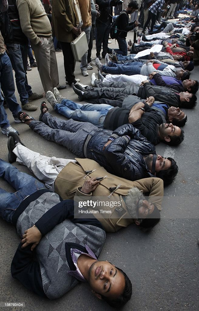 Anti-Rape protesters lying on road during gathering to mourn the death of Rape victim girl at Jantar Mantar on December 29, 2012 in New Delhi, India. The nation was shocked in the morning after news of her death at the Singapore's Mount Elizabeth Hospital, where she was undergoing treatment. The Gang-rape of 23 year old girl in a moving bus enraged the entire country and galvanized people to demand for protection for women and justice for victims of such heinous crimes. There was heavy security deployment all around the city as many roads were blocked and metro stations were closed down to prevent any untoward incident.