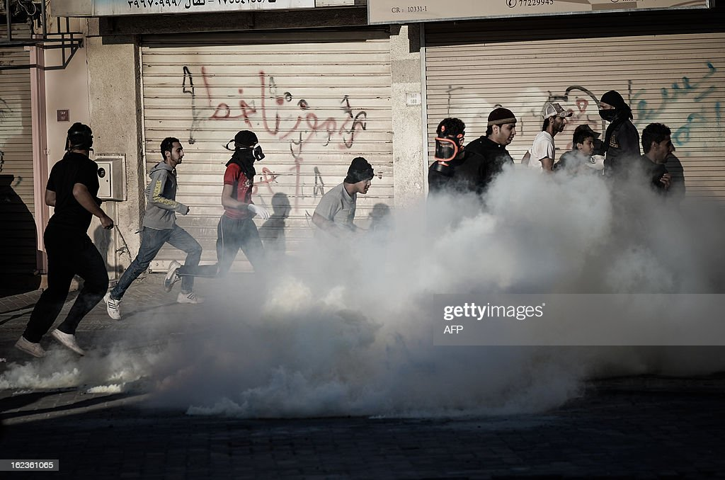 Anti-regime Bahraini protestors run for cover from tear gas and bird shots fired by riot police during clashes following a protest against the killing of 20-year old Mahmud al-Jaziri, in the village of Daih, West of Manama, on February 22, 2013. The Shiite protester died of wounds after he was shot during clashes with Bahraini police on the second anniversary of the February 14, 2011 uprising.