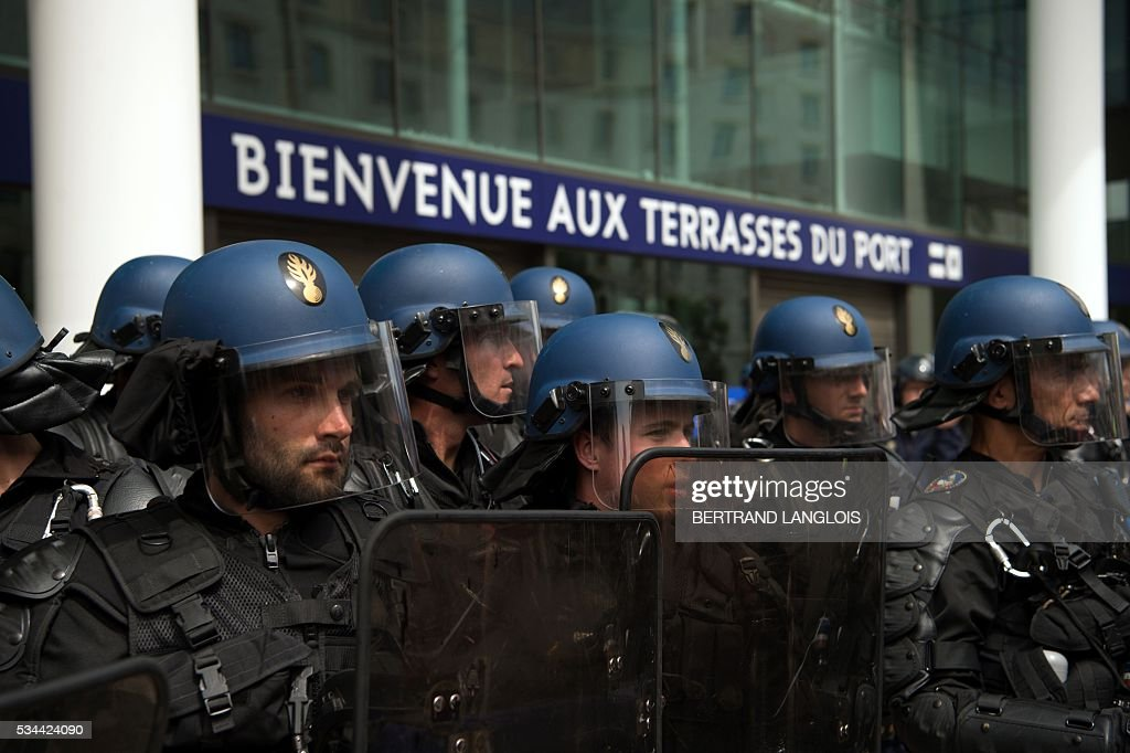 Anti-riot gendarmes protect the entrance of Les Terrasses du Port commercial centre during a demonstration against the French government's planned labour law reforms on May 26, 2016 in Marseille. The French government's labour market proposals, which are designed to make it easier for companies to hire and fire, have sparked a series of nationwide protests and strikes over the past three months. / AFP / BERTRAND