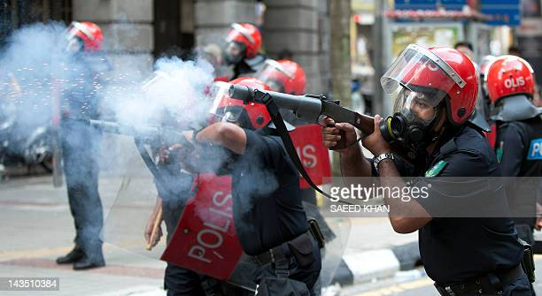 Antiriot police fire tear gas to disperse protestors during an antigovernment rally near the historical Merdeka Square in Kuala Lumpur on April 28...