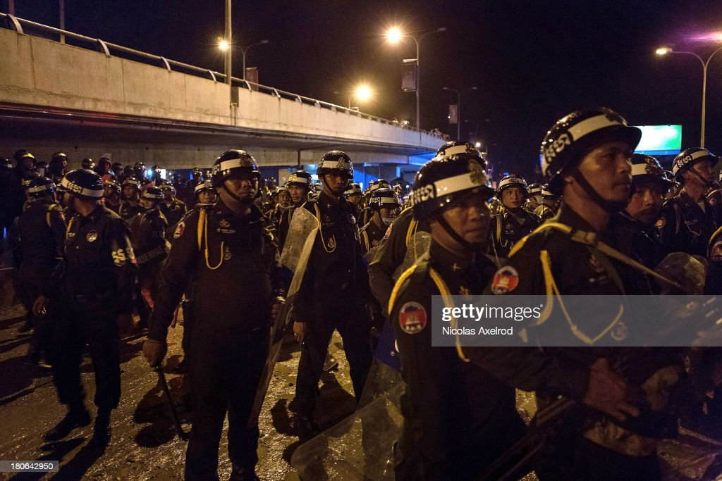Anti-riot police move in to a hanger to debrief after clashes erupted near Monivong bridge South of Phnom Penh on September 15, 2013 in Phnom Penh, Cambodia. The CNRP plan a three day demonstration to contest the Cambodian national election results.