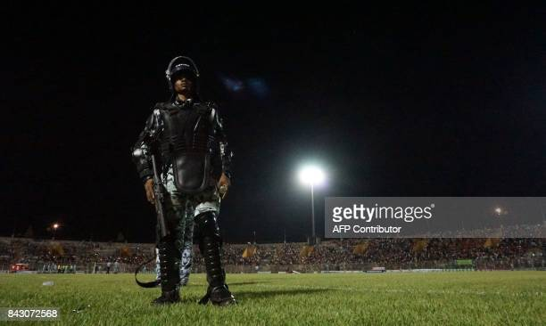 TOPSHOT Antiriot police officer stands up as fans cross the pitch during the World Cup 2018 Africa qualifying football match between Ivory Coast and...