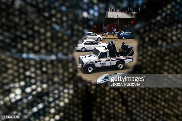 Antiriot police officers sit in the back of a police vehicle as they patrol during a demonstration by opposition parties against the introduction of...