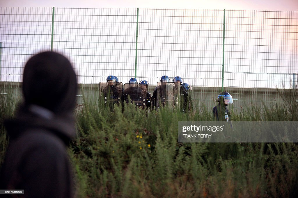 Anti-riot police officers stand next about 300 opponents to the project of an international airport in Notre-Dame-des-Landes who demonstrate in front of the Nantes-Carquefou prison in support of two activists who are incarcerated, on December 29, 2012 in Nantes, western France.