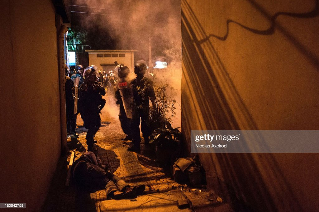 Anti-riot police prepare to shoot tear gas down an alley after beating a protestor, clashes erupted near Monivong bridge South of Phnom Penh on September 15, 2013 in Phnom Penh, Cambodia. The CNRP plan a three day demonstration to contest the Cambodian national election results.