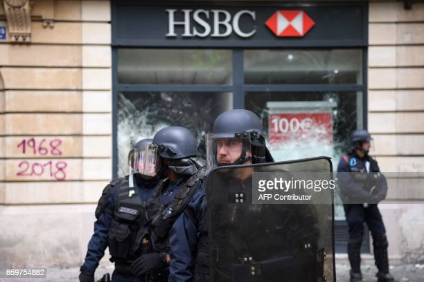 Antiriot police stand in position in front of the front window of a Swiss bank HSBC branch attacked by activists on the sidelines of a demonstration...