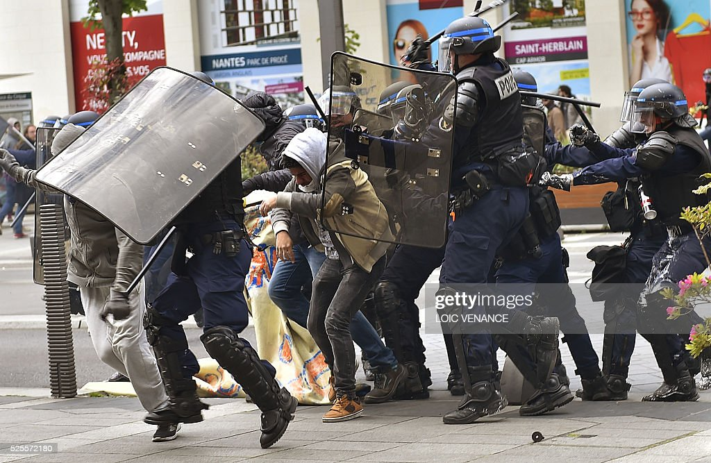 Anti-riot policemen baton charge protesters during clashes within a demonstration against the French government's proposed labour reforms on April 28, 2016 in Nantes. Protests turned violent in Paris and other French cities today as tens of thousands of workers and students made a new push for the withdrawal of a hotly contested labour bill. / AFP / LOIC