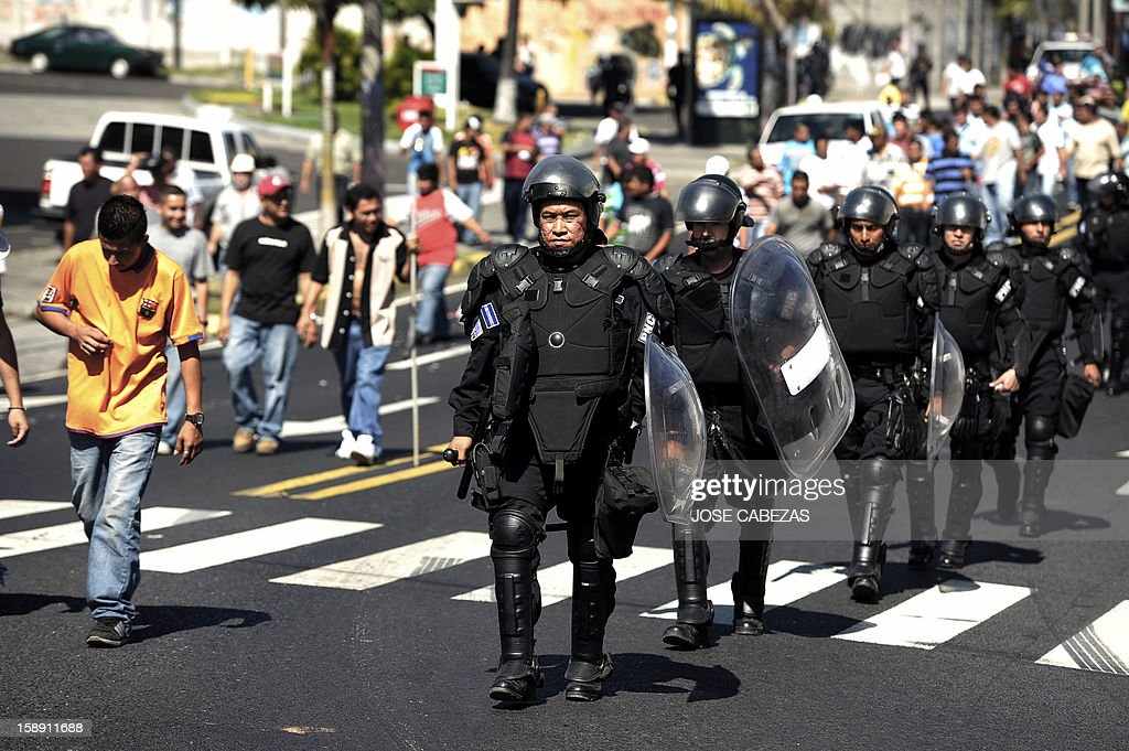 Anti-riot policemen custody a group of bus drivers as they protest in San Salvador, on January 3, 2013. Bus owners and drivers called for a strike in demand of a rise in the price of the ticket for the buses of public transportation. AFP PHOTO/ Jose CABEZAS