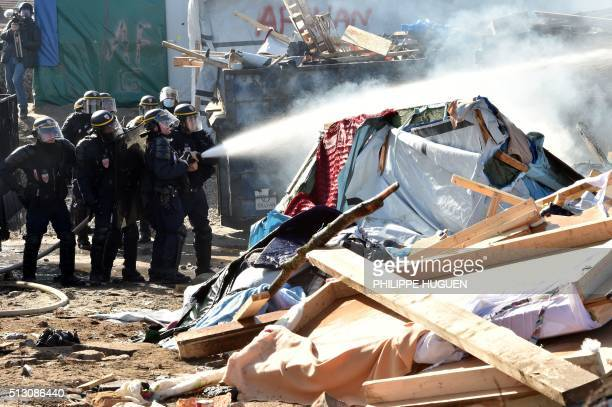 TOPSHOT Antiriot policemen extinguish a fire during the dismantling of half of the 'Jungle' migrant camp in the French northern port city of Calais...