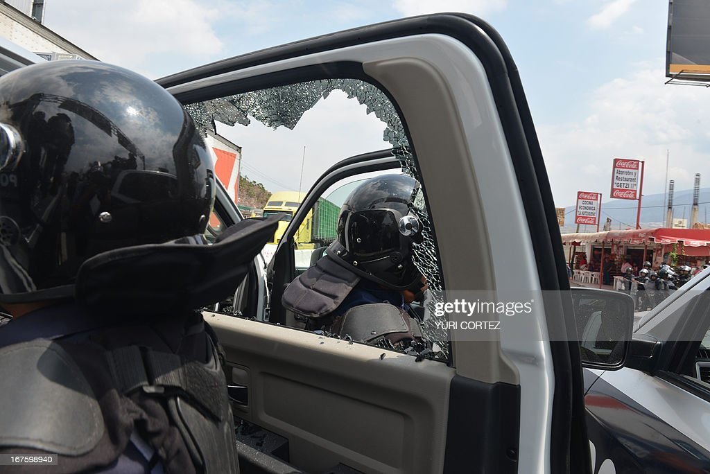 Anti-riot policemen observe a damaged patrol van by teachers and students during a protest against the educative reform in Chilpancingo, Guerrero state, Mexico on April 26, 2013. AFP PHOTO/ Yuri CORTEZ