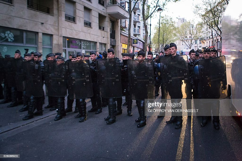 Anti-riot policemen stand guard the street during the Jean-Jaur��s highschool evacuation in Paris on May 4, 2016. The police evacuated this morning a highschool under construction occupied by 200 migrants in northeatern Paris since two weeks, while protesters clashed with policemen outside the building. / AFP / GEOFFROY