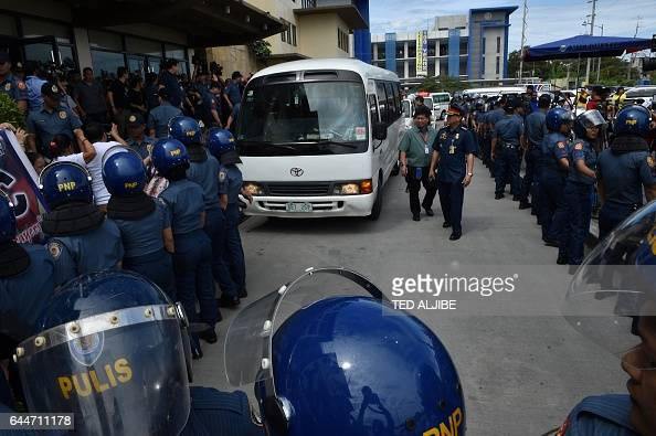 Antiriot policemen suround the vehicle transporting Senator Leila De Lima a top critic of President Rodrigo Duterte as she arrives outside the court...