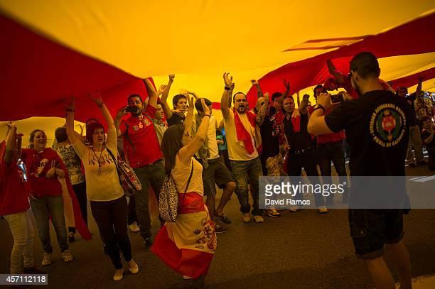 Antiseparatist Catalans shout slogans under a huge half catalan half spanish flag during a demonstration on October 12 2014 in Barcelona Spain...