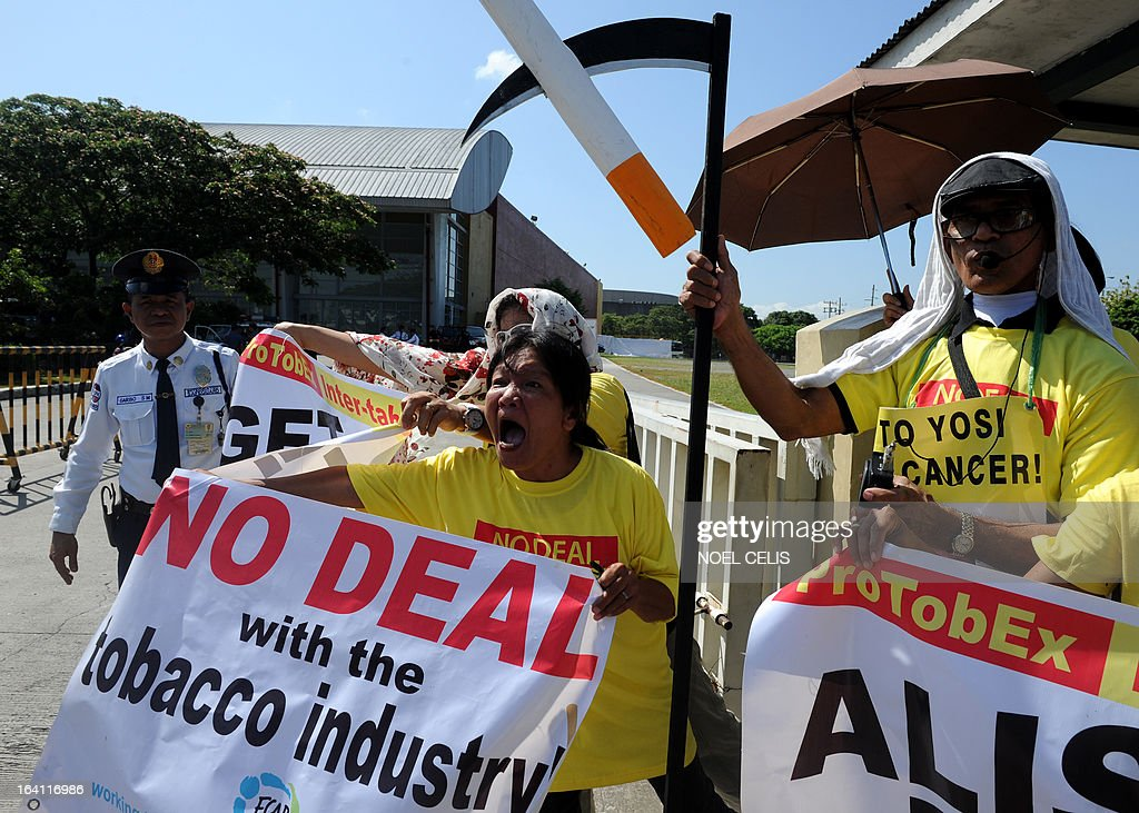 Anti-smoking protesters hold banners and shout as foreign delagates drive past inside a car (not pictured) during a protest at the entrance gate of the World Trade Center in Manila on March 20, 2013 where the world's biggest tobacco trade show is being held. The United Nations has expressed concern that the Philippines could encourage smoking by hosting one of the world's biggest tobacco trade shows, a health official said on March 20. UN agencies in the Philippines have written to President Benigno Aquino citing Manila's treaty pledge to ban tobacco advertising, promotion and sponsorship, World Health Organisation senior health adviser Eigil Sorensen said. AFP PHOTO / NOEL CELIS