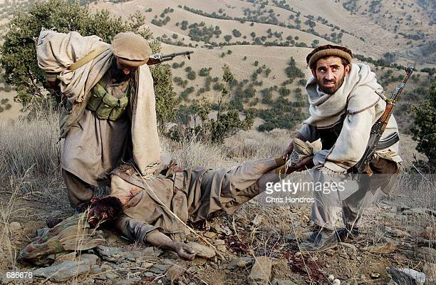 AntiTaliban soldiers carry off the body of an al Qaeda soldier they just killed in battle December 11 2001 in the Tora Bora area of Afghanistan...