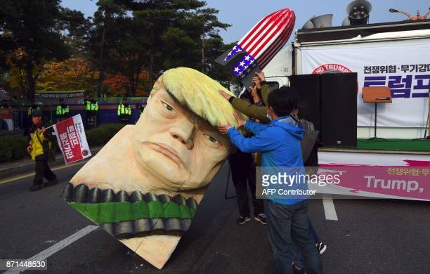 AntiTrump portestors set an effigy of US President Donald Trump during a rally near the National Assembly in Seoul on November 8 2017 as Trump is due...