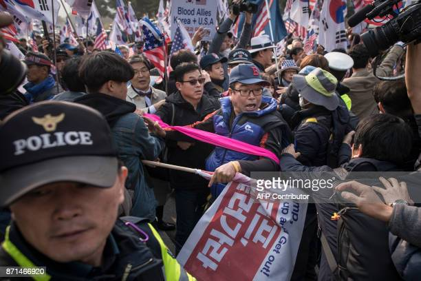 AntiTrump protesters attempt to stop US/Trump supporters from entering their rally outside the National Assembly in Seoul on November 8 2017 US...