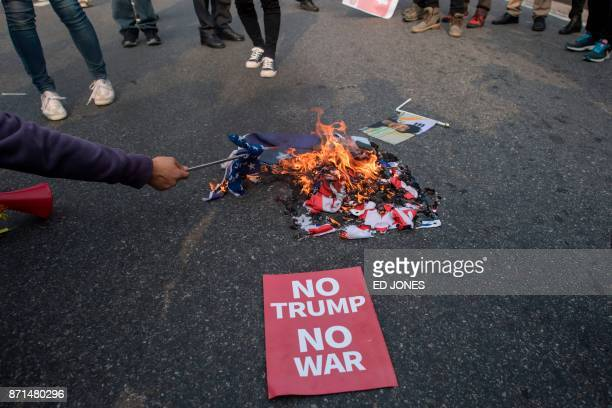 AntiTrump protesters burn US flags during a rally outside the National Assembly where US President Donald Trump was speaking in Seoul on November 8...
