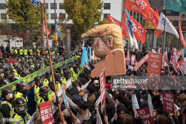 TOPSHOT AntiTrump protesters hoist a giant bust depicting US President Donald Trump towards police during a rally outside the National Assembly where...