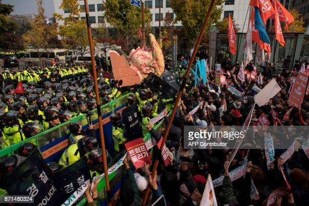 AntiTrump protesters hoist a giant bust depicting US President Donald Trump towards police during a rally outside the National Assembly where Trump...
