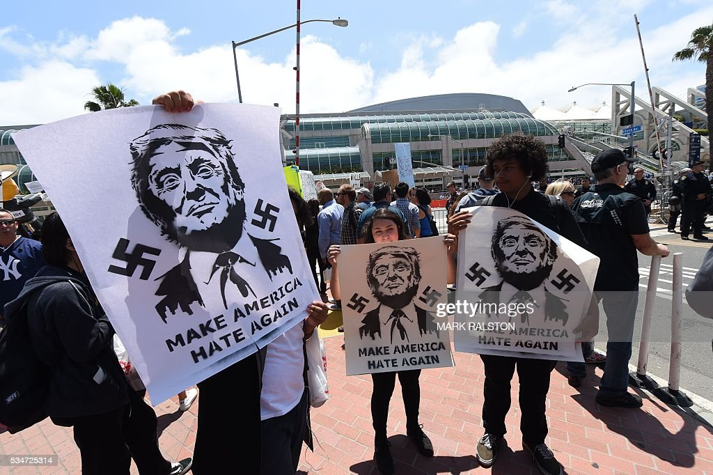 Anti-Trump protesters hold signs up outside a venue where republican presidential candidate Donald Trump will speak in San Diego, California on May 27, 2016. / AFP / Mark Ralston