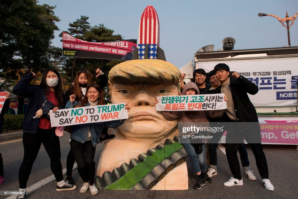 Anti-Trump protesters pose for a photo with a statue depicting US President Donald Trump during a rally outside the National Assembly in Seoul on November 8, 2017. US President Donald Trump offered North Korean leader Kim Jong-Un what he called 'a path towards a much better future' as tensions soar over Pyongyang's nuclear ambitions. / AFP PHOTO / Ed JONES
