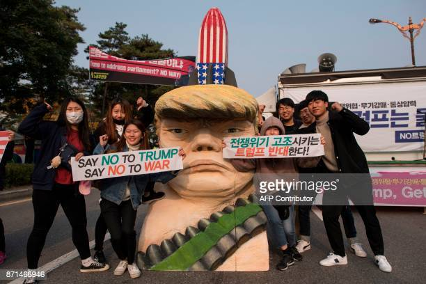 AntiTrump protesters pose for a photo with a statue depicting US President Donald Trump during a rally outside the National Assembly in Seoul on...