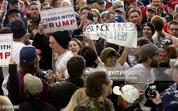 AntiTrump protestors at Republican Presidential hopeful Donald Trump's rally at Synergy Flight Center on March 13 2016 in Bloomington Illinois / AFP...