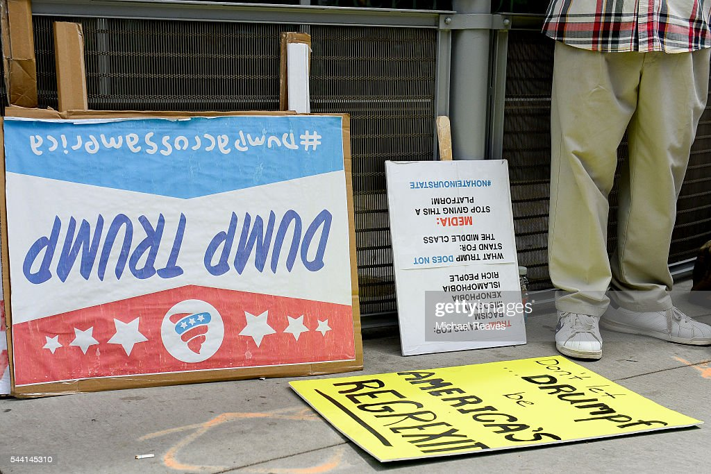 Anti-Trump signs sit on the ground outside the Western Conservative Summit on July 1, 2016.