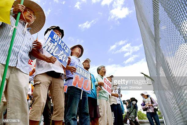AntiUS base relocation protesters demonstrate outside the US Camp Schwab as the construction work of a new US base resumes on September 12 2015 in...