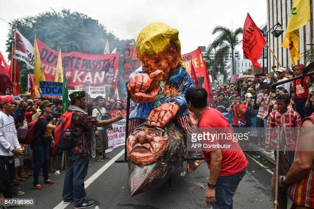 AntiUS protesters burn effigies of US President Donald Trump and Philippine President Rodrigo Duterte during a rally near the US embassy in Manila on...