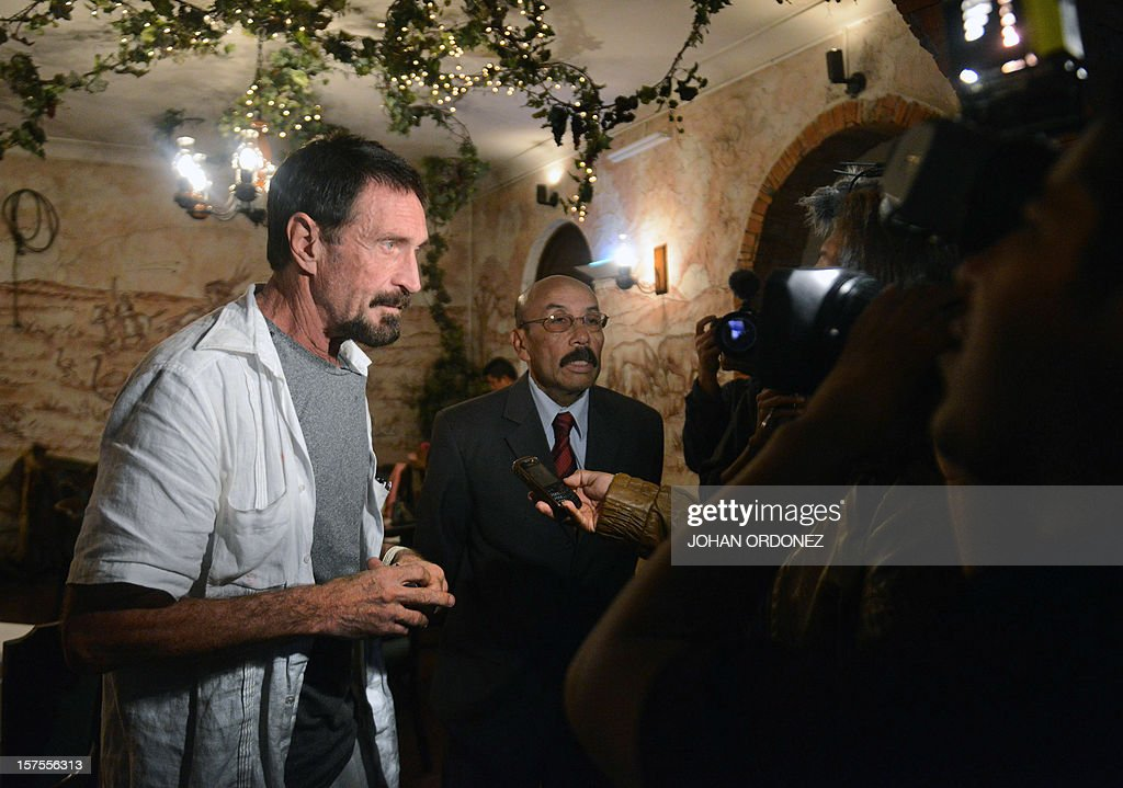 US anti-virus software pioneer John McAfee (L) and his Guatemalan lawyer Telesforo Guerra (C) answer questions to a journalist, in a restaurant in Guatemala City on December 04, 2012. McAfee, wanted for questioning over the murder of his neighbor last month in Belize, is seeking political asylum in Guatemala. AFP PHOTO / Johan ORDONEZ