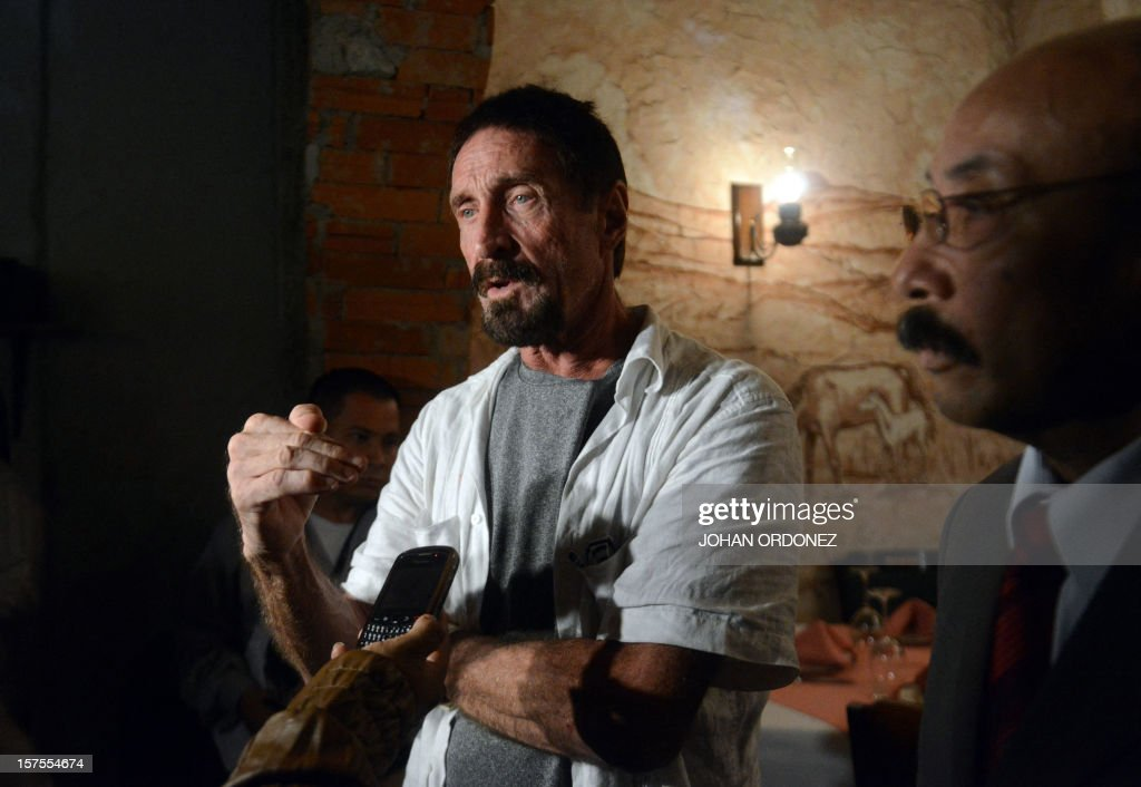 US anti-virus software pioneer John McAfee (L) answers questions to a journalist next to his Guatemalan lawyer Telesforo Guerra (R), in a restaurant in Guatemala City on December 04, 2012. McAfee, wanted for questioning over the murder of his neighbor last month in Belize, is seeking political asylum in Guatemala. AFP PHOTO / Johan ORDONEZ