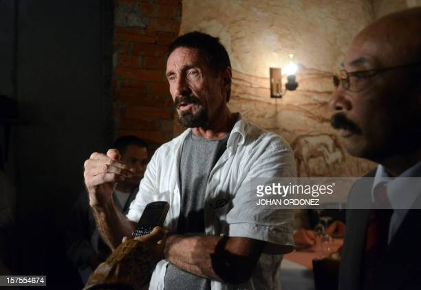 US antivirus software pioneer John McAfee answers questions to a journalist next to his Guatemalan lawyer Telesforo Guerra in a restaurant in...