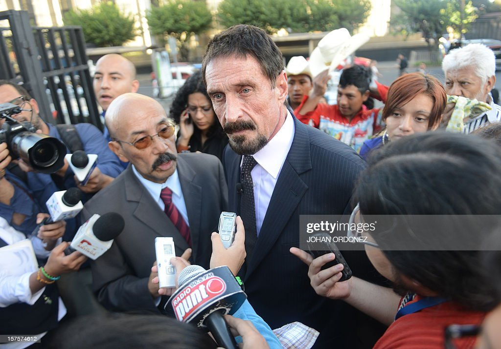 US anti-virus software pioneer John McAfee (R) answers questions to journalistas next to his Guatemalan lawyer Telesforo Guerra (L), in front of the Supreme Court in Guatemala City on December 04, 2012. McAfee, wanted for questioning over the murder of his neighbor last month in Belize, is seeking political asylum in Guatemala. AFP PHOTO / Johan ORDONEZ